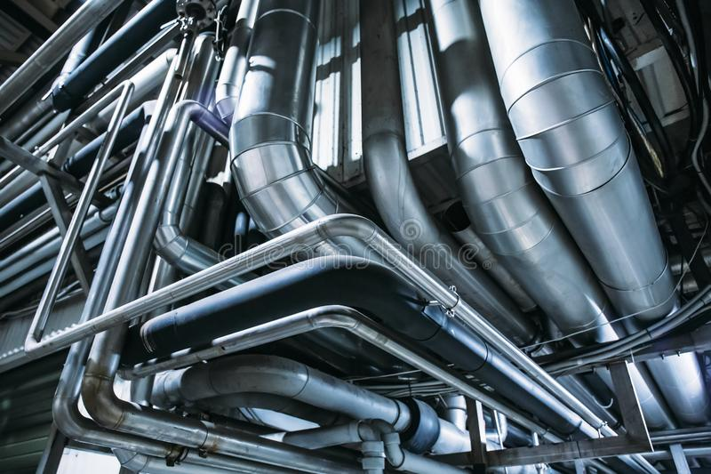 Industrial steel pipes or tubes of air ventilation system as abstract industry equipment background. In blue tones stock image