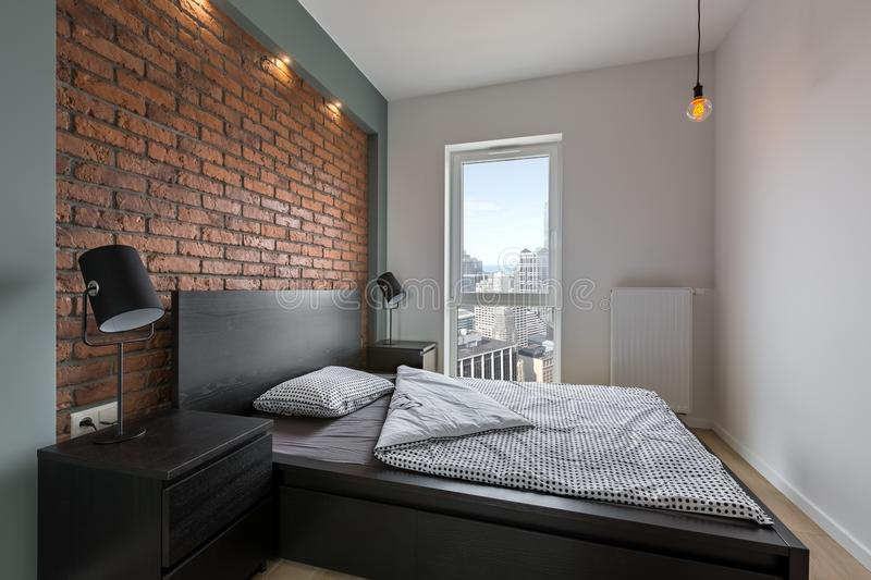 Industrial style bedroom with bed stock photography