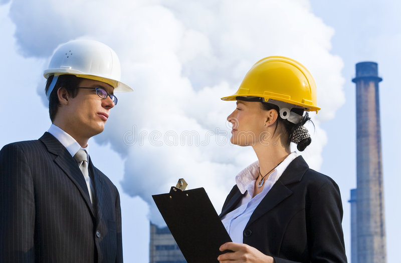 Industrial Teamwork. Young male and female managers working together in an industrial situation with royalty free stock images