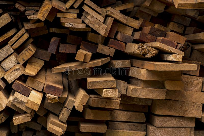 Industrial timber for construction. Old wood used to translate the picture. Piled stack of natural brown uneven rough wooden boards lit royalty free stock image