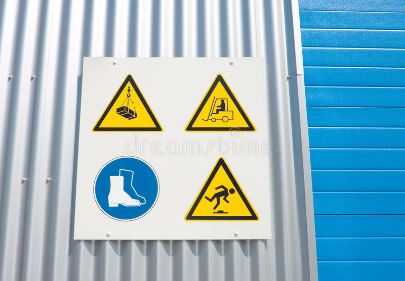 Industrial warning signs. On a warehouse with a blue roller door stock photography
