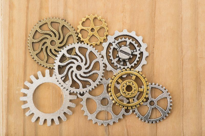 Industrial wheels. In copper and silver on wooden background stock photo