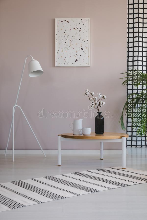 White lamp next to wooden coffee table with cotton flower in black vase, coffee cups and jug royalty free stock photo