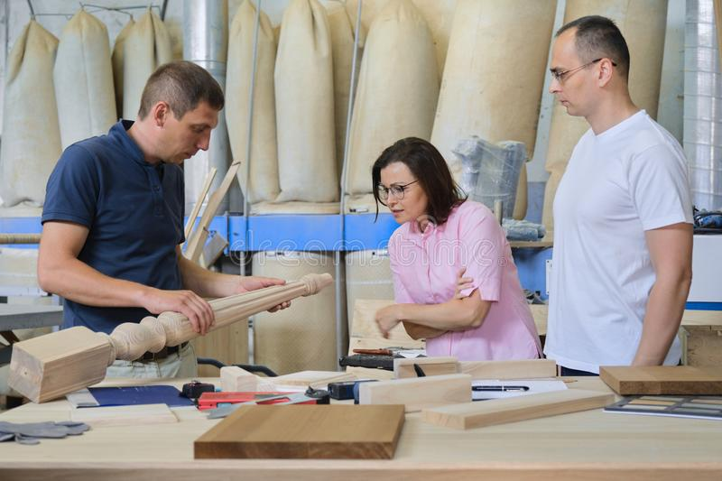 Industrial woodworking workshop, team of people discussing carpentry process. New products royalty free stock images