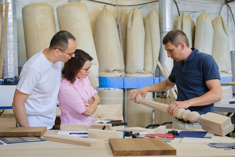 Industrial woodworking workshop, team of people discussing carpentry process. New products royalty free stock photo