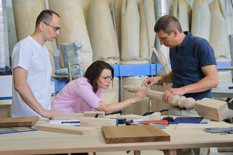 Industrial woodworking workshop, team of people discussing carpentry process. New products royalty free stock image