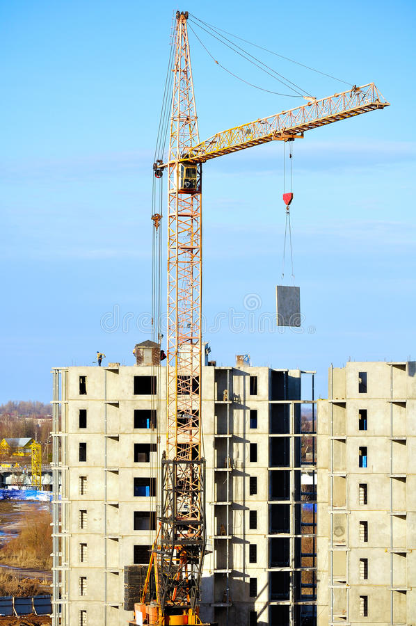 Industrial work at building site - lifting of concrete slab by tower crane. View from height. Construction of a residential house - lifting of concrete slab by royalty free stock photo