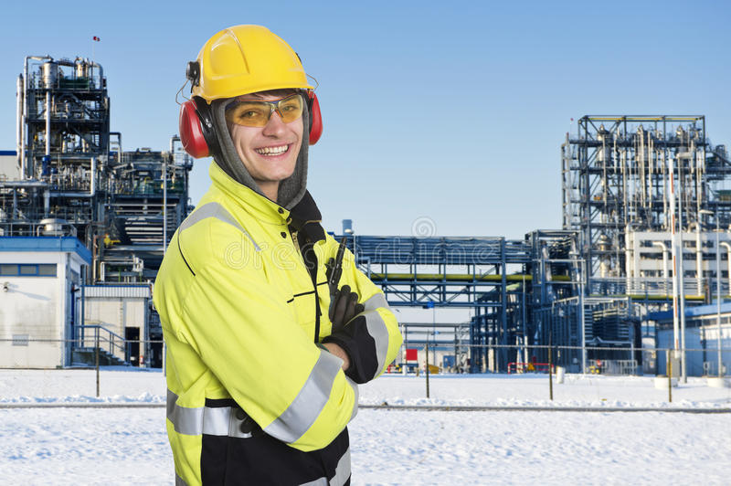 Industrial worker. Posing in front of the main gate of a large chemical plant. Wintertime. Happy engineer, wearing all safety clothing necessary, such as royalty free stock image