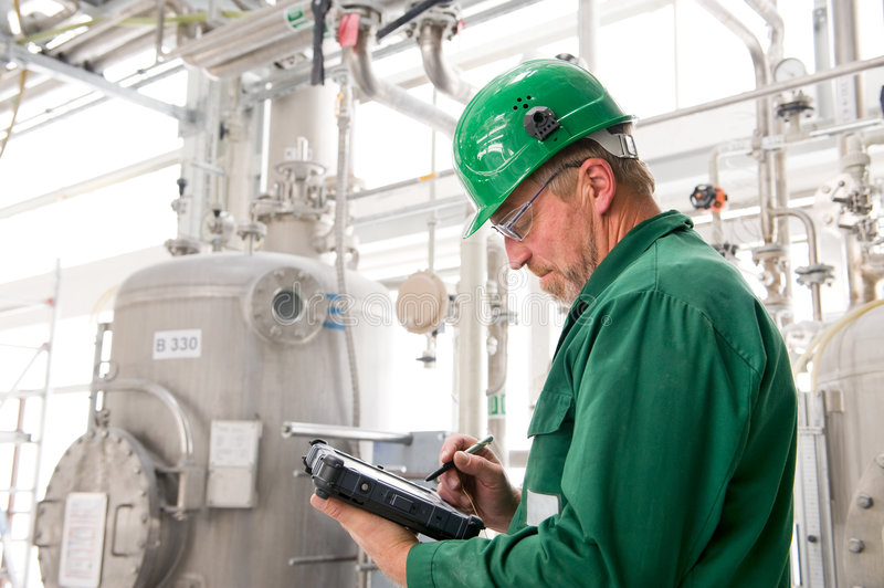Industrial worker. Middle aged industrial worker with notebook royalty free stock photo