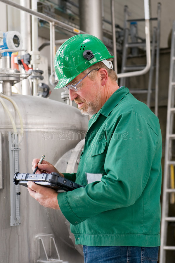 Industrial worker. Middle aged industrial worker with notebook stock image