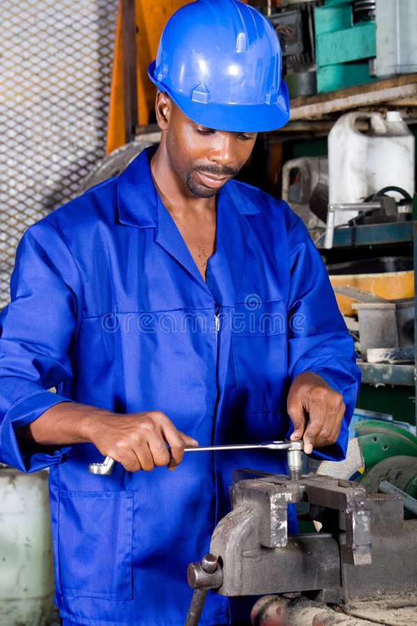 Industrial worker. Young african american industrial worker doing repair jobs royalty free stock photo