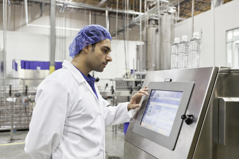 Industrial worker at bottling machine stock photos