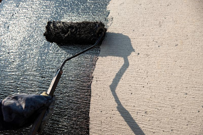 Industrial worker on construction site laying sealant. For waterproofing cement. Black roof coating stock images