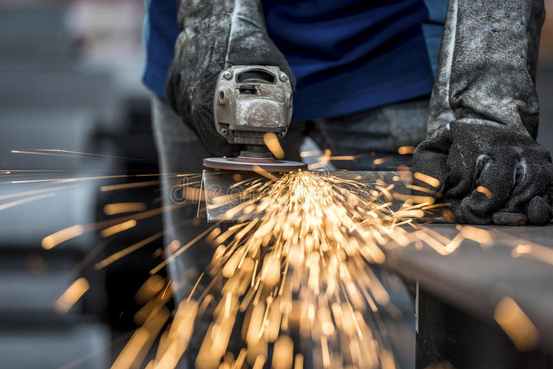 Industrial worker cutting metal. With many sharp sparks royalty free stock photography