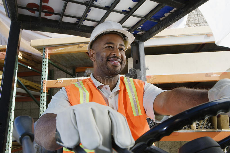 Industrial Worker Driving Forklift At Workplace. Happy male industrial worker driving forklift at workplace stock photo