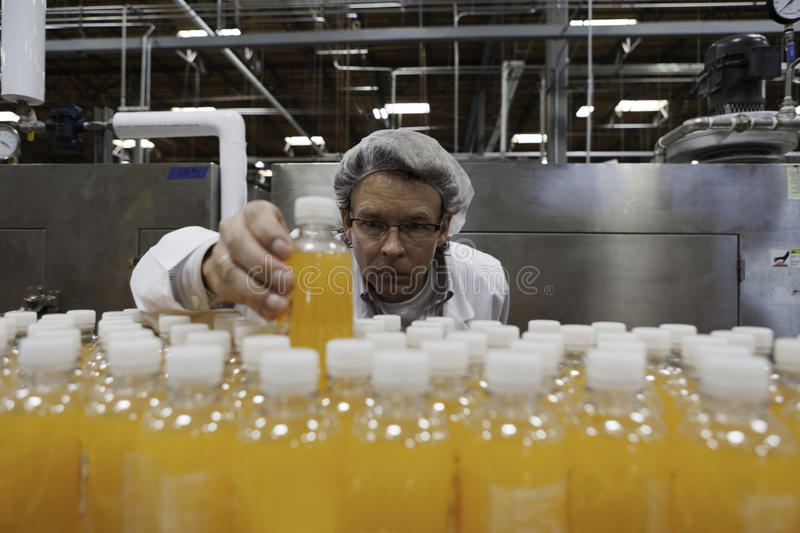 Industrial worker examining bottle in factory stock photos
