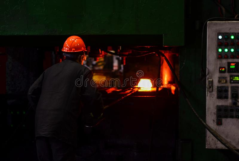 Industrial Worker at the factory welding closeup. Hot iron in smeltery held by a worker royalty free stock photography