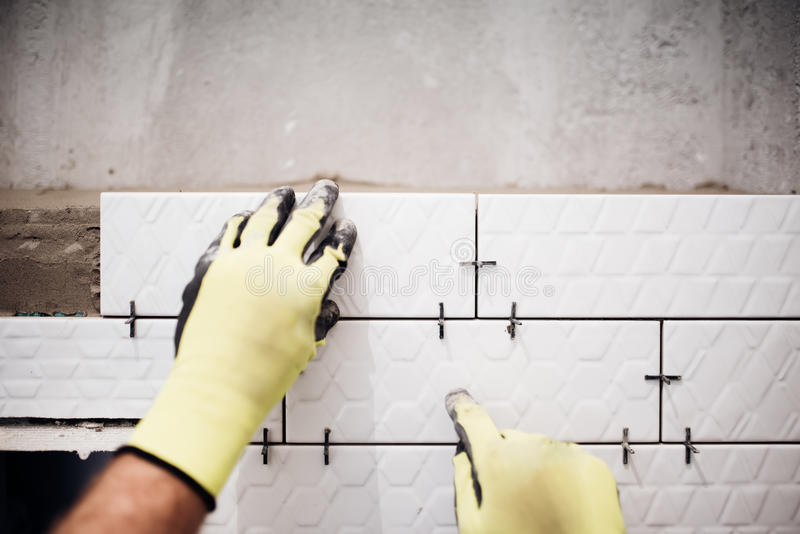 industrial worker installing small ceramic tiles in bathroom during renovation works stock image