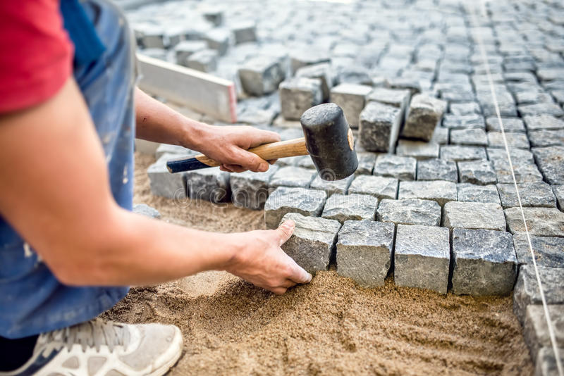 Industrial worker installing stone blocks on pavement, street or sidewalk construction works royalty free stock photo
