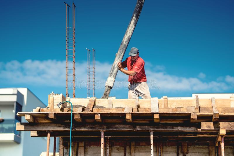 Industrial worker laying concrete with automatic tube pump. Workman on site with mortar and construction activities stock images