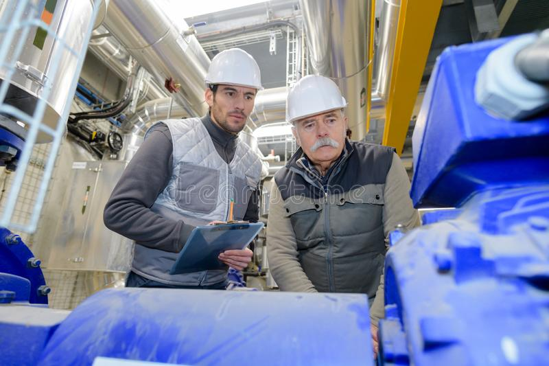 Industrial worker looking at production material stock image