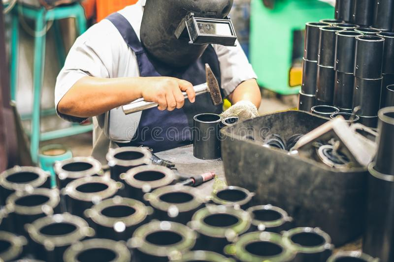 Industrial worker in manufacturing plant grinding to finish a Metal pipe. Industrial Worker at the factory welding closeup royalty free stock images