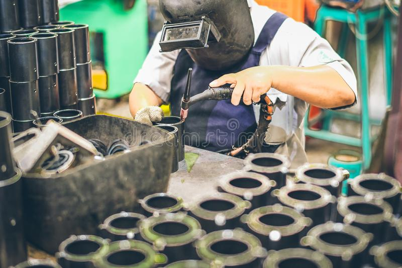 Industrial worker in manufacturing plant grinding to finish a Metal pipe. Industrial Worker at the factory welding closeup royalty free stock photography