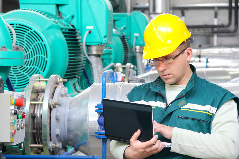 Industrial worker with notebook. In a factory stock photography