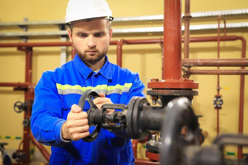 Industrial worker opens water valve on heating boiler system royalty free stock image
