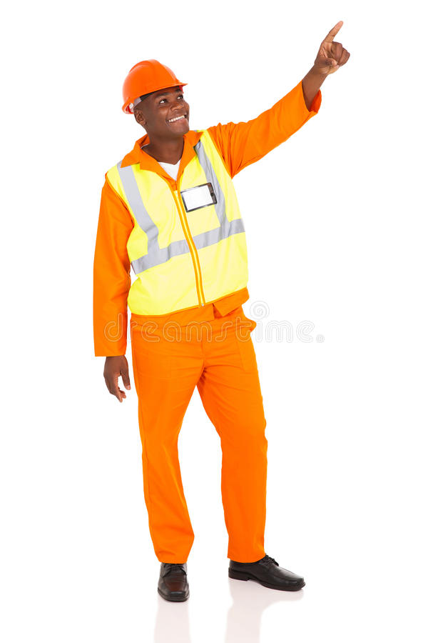 Industrial worker pointing. Happy african american industrial worker pointing on white background stock photography