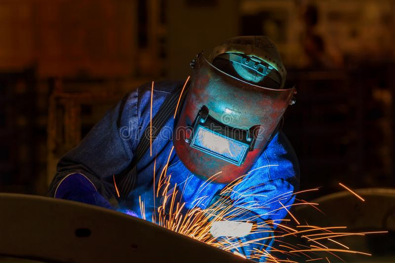 Industrial worker is welding assembly automotive part in car factory royalty free stock photos