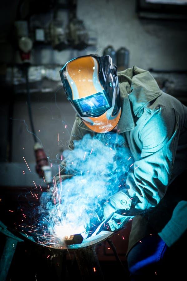 Industrial worker welding. Industrial worker at the factory welding steel construction stock photography