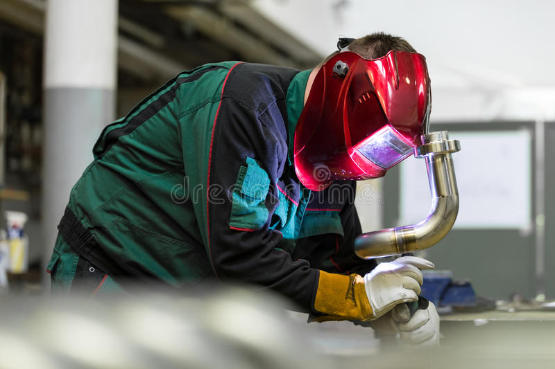 Industrial worker welding in metal factory. Industrial worker with protective mask welding inox elements in steel structures manufacture workshop stock photo
