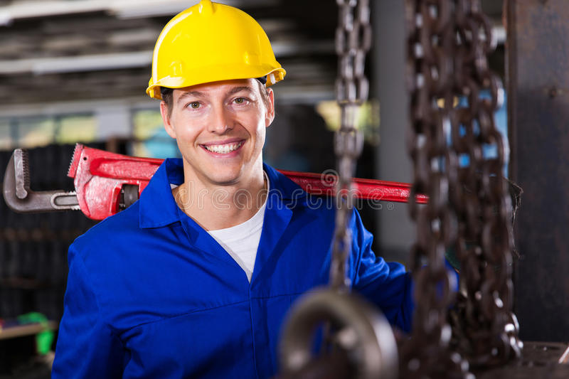 Industrial worker wrench. Industrial worker carrying monkey wrench in workshop royalty free stock images