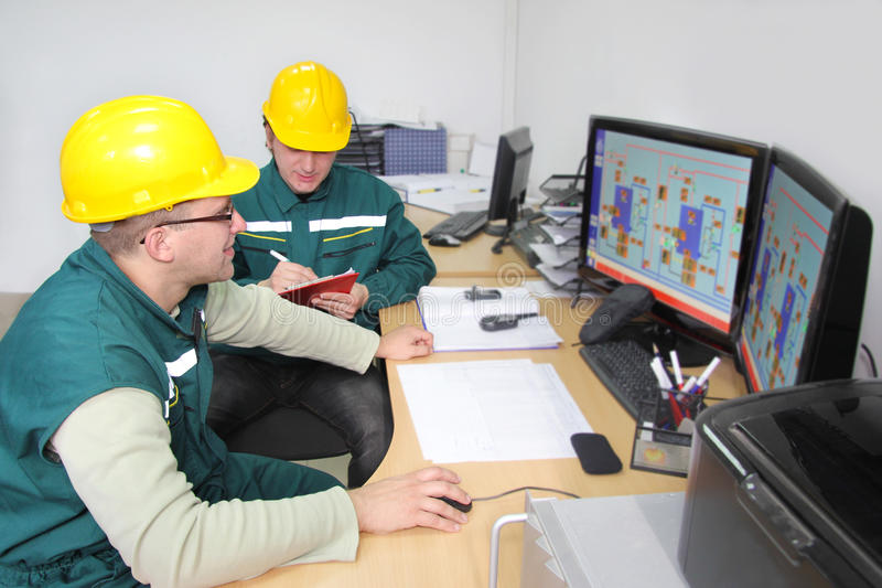 Industrial workers in a control room. Industrial workers with computer in a control room