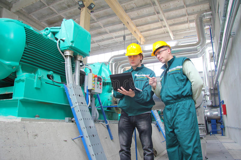 Industrial workers with notebook. Working in power plant, teamwork
