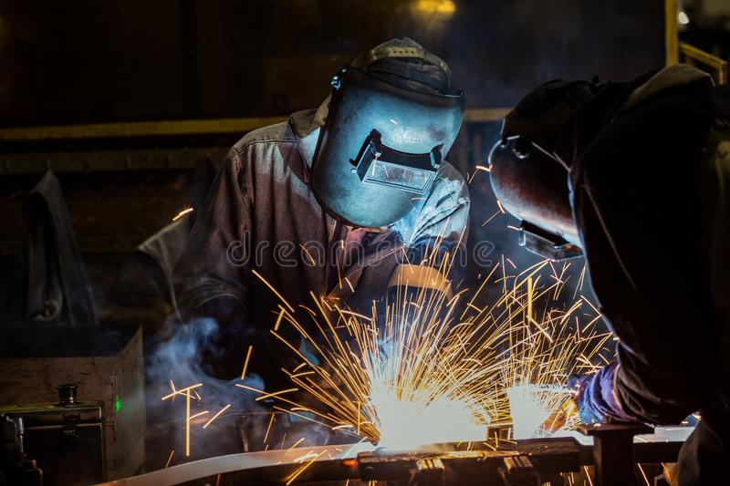 Industrial workers are welding merging automotive part in car factory. Industrial workers are movement welding merging automotive part in car factory stock photography