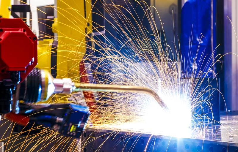 Industrial yellow robot welder close - up conduct welding of metal parts, metal droplets are beautifully sprinkled in royalty free stock photography