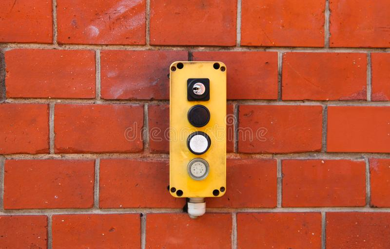 Industrial yellow switch box with power on and off switches buttons and key lock installed outdoors on a red brick wall from wareh stock photography