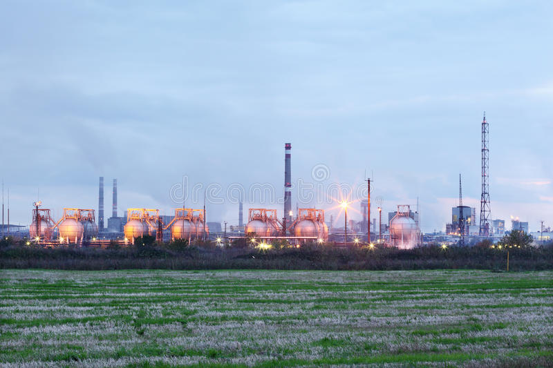 Industrial zone with factories and pipes with smoke. And illumination at evening royalty free stock image