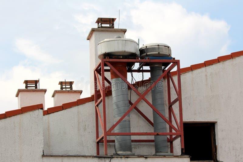 Industriale multiplo del metallo e camini concreti regolari sopra il piccolo tetto di costruzione coperto di mattonelle di tetto  fotografia stock