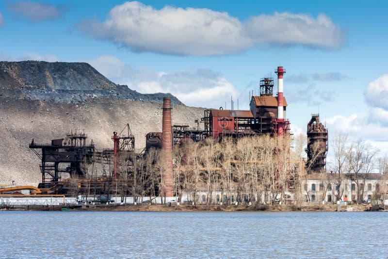 Industrianläggning nära sjön mot bakgrunden av en enorm förrådsplats royaltyfri foto