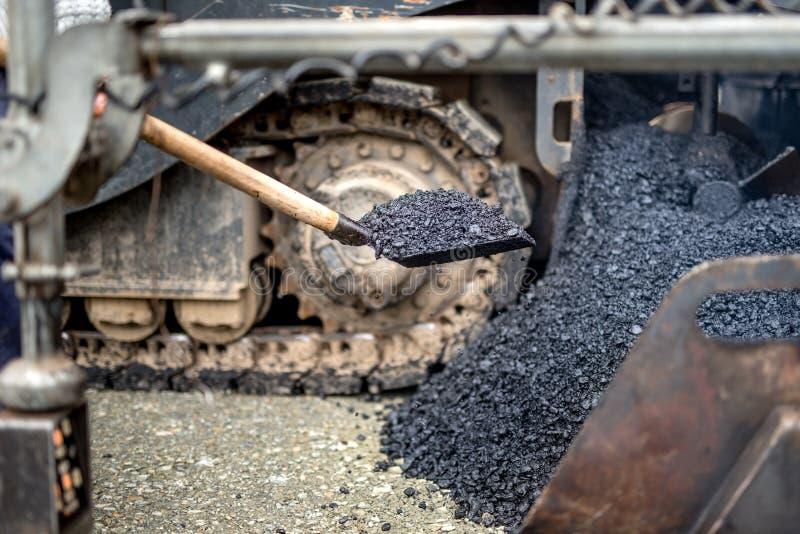 Industriarbetare faktotum som använder skyffeln för bärande asfalt på vägkonstruktion royaltyfri foto