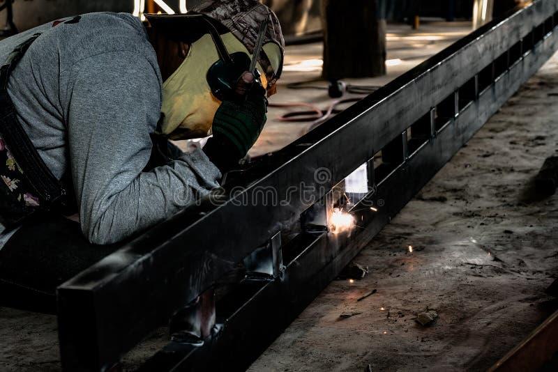 Industriarbetare p? fabrikssvetsningcloseupen Elektriskt hjul som maler p? st?lstrukturen i fabrik arkivbild