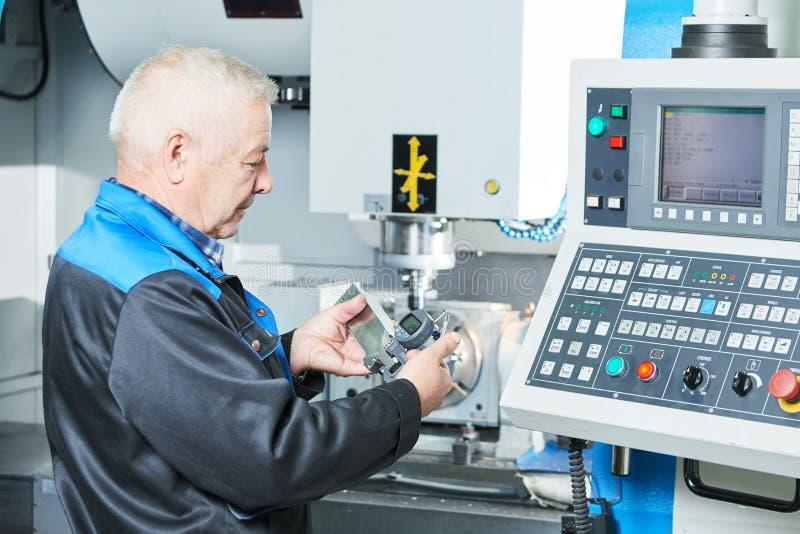 Industriarbetare som mäter detaljen nära cnc-malningmaskinen royaltyfri bild