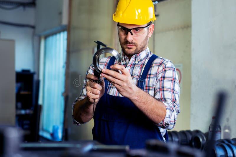 Industriarbetareinspektör som mäter detaljen med Vernier Caliper fotografering för bildbyråer