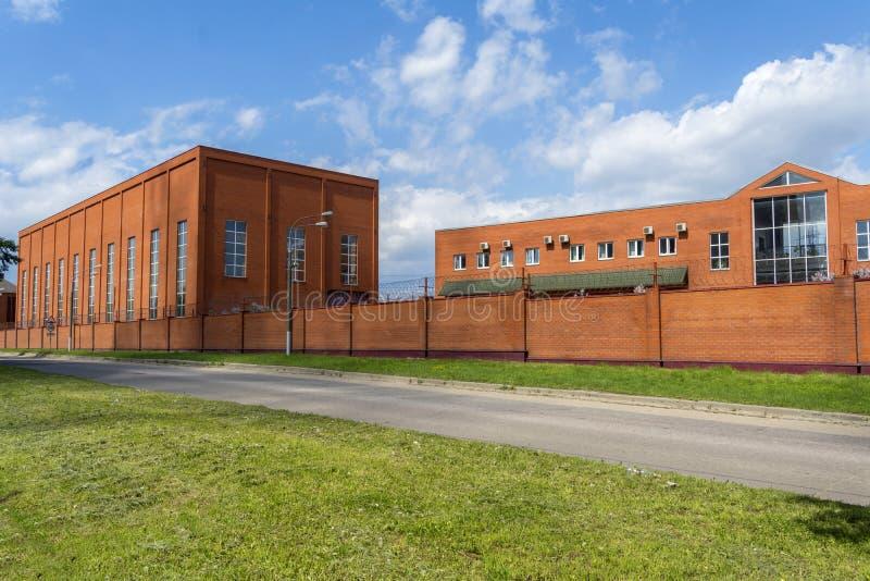 Industribyggnad med kontorsbyggnad Produktionrum som göras av tegelsten Staket för röd tegelsten liten fabrik royaltyfria bilder