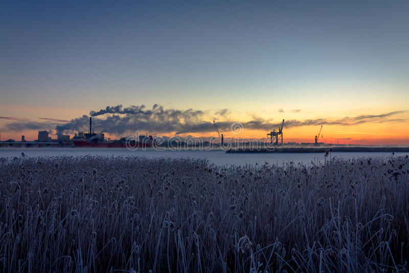 Industrie avec des cheminées de fumée et le paysage tubulaire de nature dans le lever de soleil image libre de droits