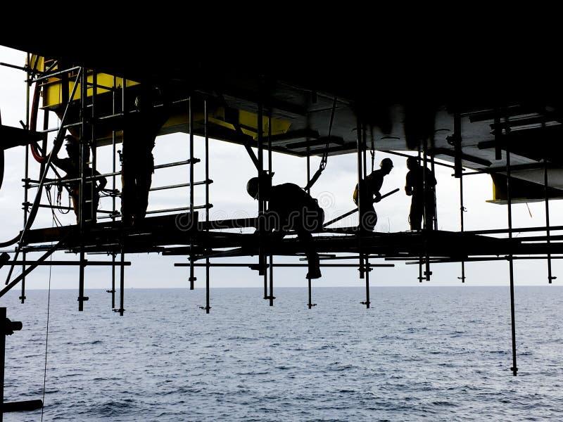 Industrie van de olie en van het Gas Silhouet van zeearbeiders met daling p stock fotografie