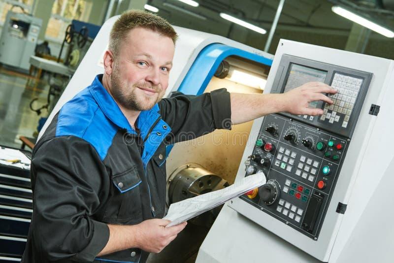 Industriearbeiter, der cnc-Drehmaschine in Metallbearbeitungsindustrie betreibt stockfoto